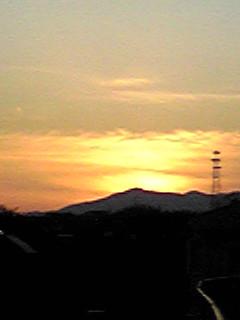 大山に沈んだ夕日と飛行機雲
